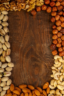 Frame of scattered assorted nuts on a wooden table. copy space.