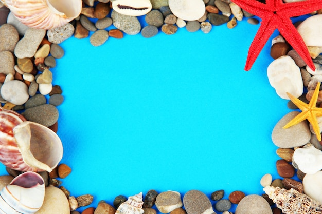 Frame of sea stones on color background