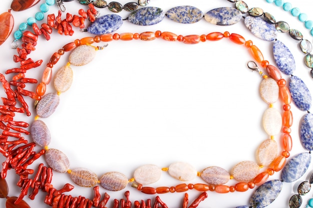 Frame of semiprecious stone beads on white surface