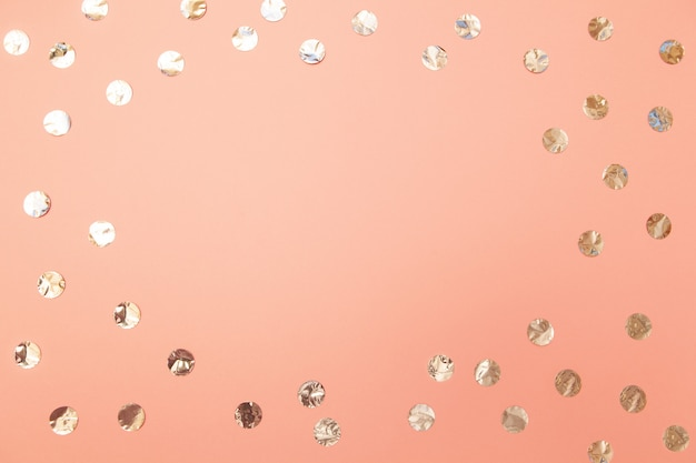 Frame of shiny silver confetti on pastel millennial pink paper background.