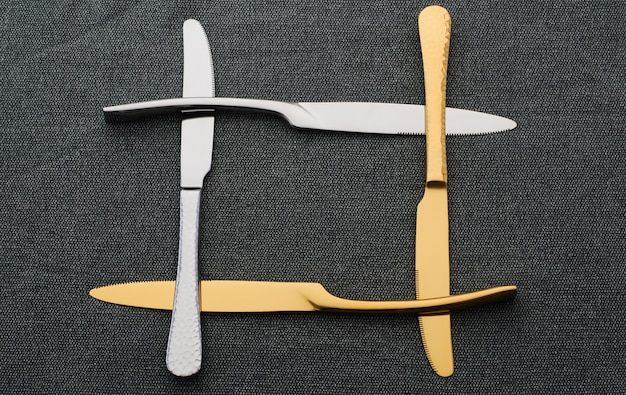 Frame of silver and gold knives on a dark tablecloth. set of metal knives