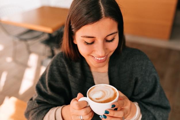 Cornice sopra di sorridente felice donna dai capelli scuri che beve il caffè nella caffetteria