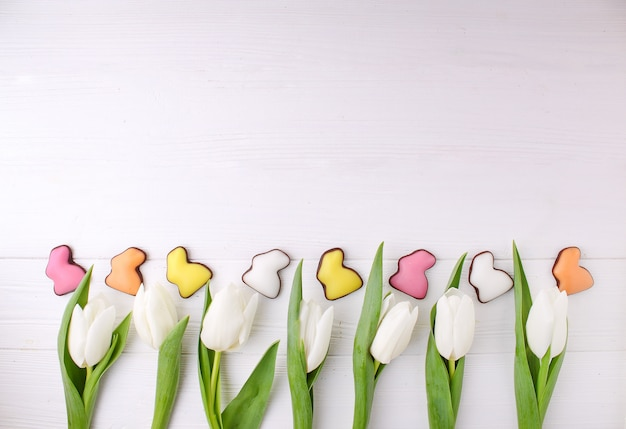 Frame of sweets for celebrate easter. chocolate colorful bunny and white tulips.