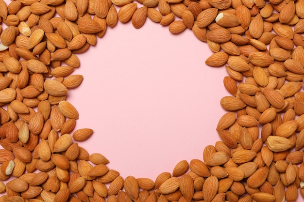 Frame of tasty almond on pink background, space for text