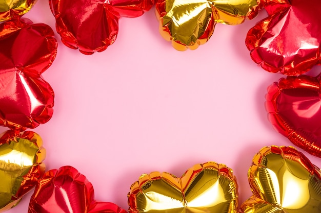 Frame for text with red and golden hearts foil balloons upper view on pink
