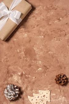 フレームの上面図は、白いリボン、松ぼっくり、木製のヘリンボーン装飾が施されたクリスマスギフトボックスのモックアップです。コピースペースのあるベージュのテクスチャ背景にフラットレイ。