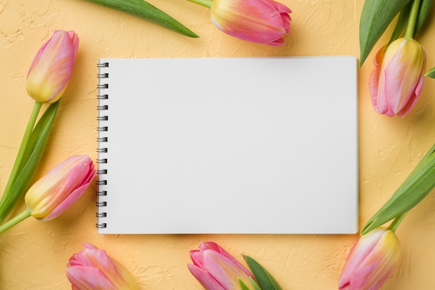 Frame of tulips beside notebook