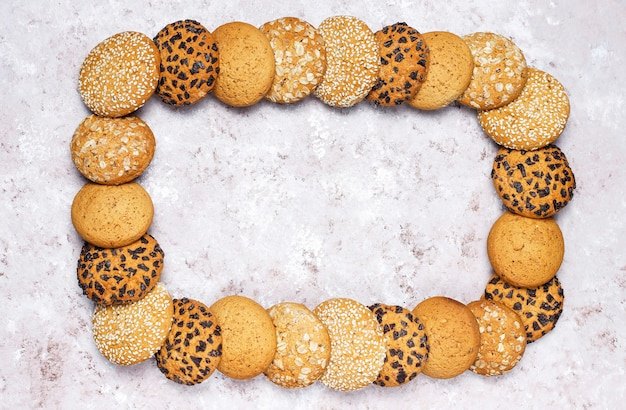 Frame of various american style cookies on a light concrete background. shortbread with confetti, sesame seed, peanut butter, oatmeal and chocolate chip cookies.