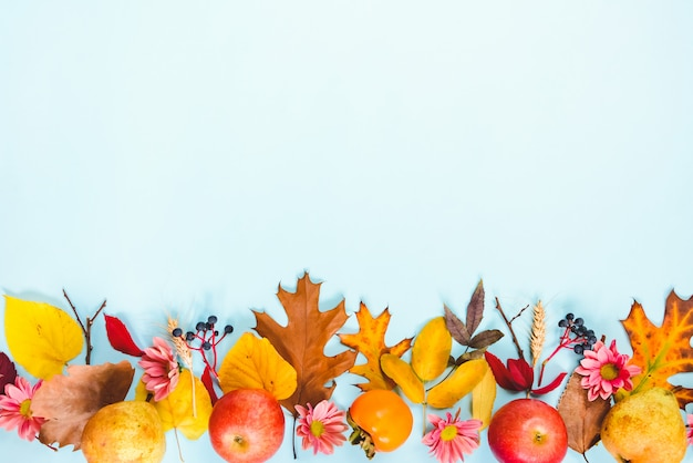 A frame of various colorful autumn fruits and leaves over light blue background.
