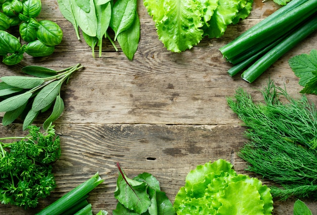 Frame of various fresh herbs on old wooden background