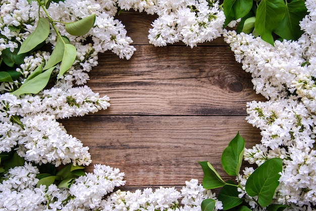 Frame of white lilac on a wooden background