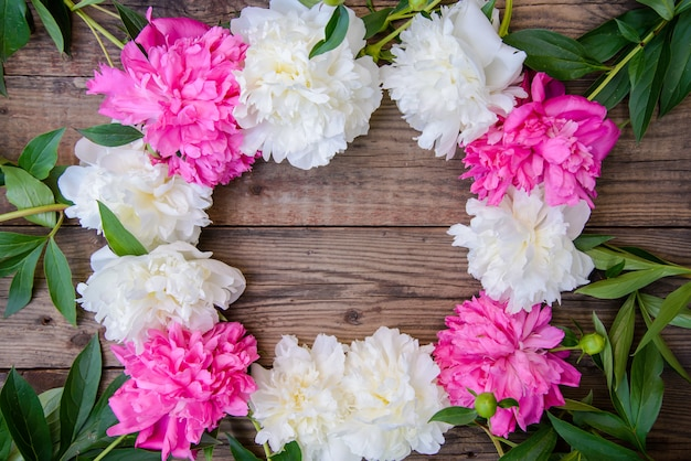 Frame of white and pink peonies on wooden background