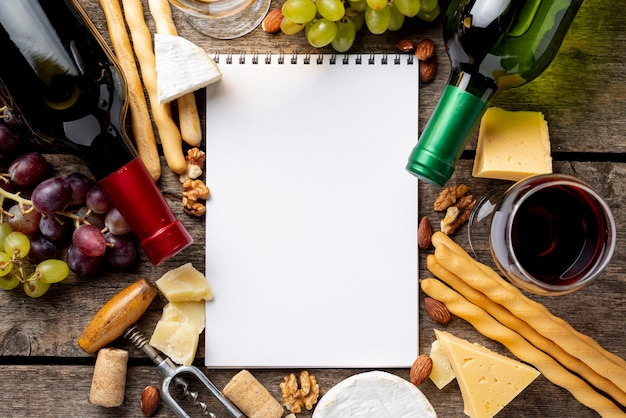 Frame of wine bottles and snack beside notebook