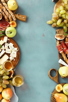 Frame wine snacks fruit jamon cheese frame background top view
