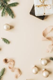 ベージュの表面にモミの針の枝、ギフトボックス、リボン、クリスマスつまらないもので作られた空白のコピースペースのあるフレーム