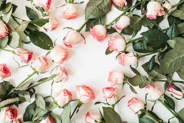 白地にピンクのバラの花で作られた空白のコピースペースのモックアップとフレーム