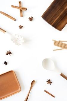 台所用品、シナモン、アニス、木製のまな板、スプーン、白い表面の皿で作られた空白のモックアップコピースペースとフレーム
