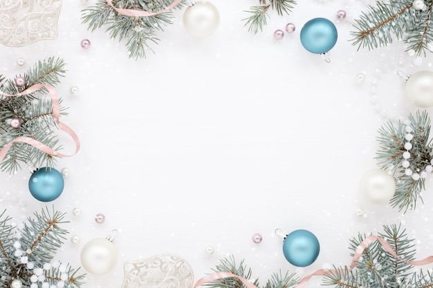 Frame with blue christmas decorations and fir tree on white surface