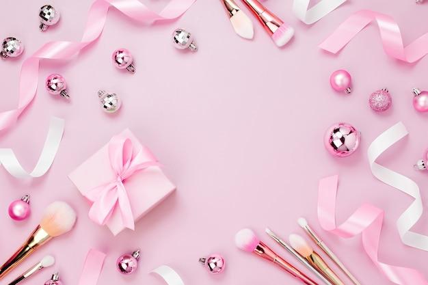 パステルピンク色のクリスマスボール、ギフト、リボン、化粧品、装飾品のフレーム。休日の背景。美容コンセプト。フラットレイ、上面図