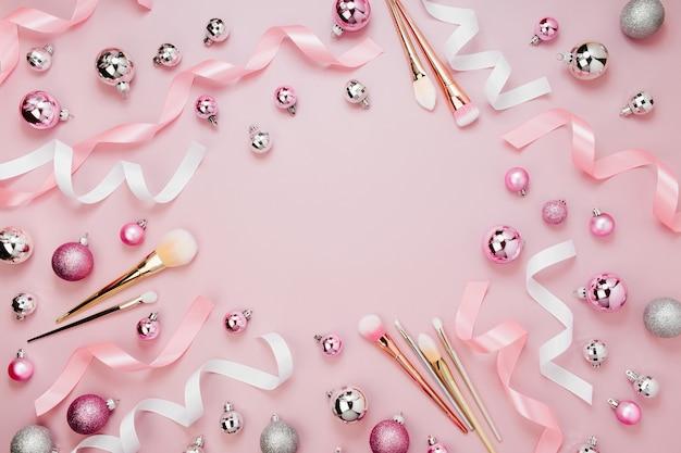 クリスマスボール、リボン、化粧ブラシ、パステルピンク色の装飾が施されたフレーム。休日の背景。美容コンセプト。フラットレイ、上面図