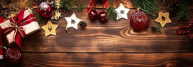 Рамка с рождественским декором на деревянном фоне. новый год, атмосфера праздника, зеленые еловые ветки, украшения: звездочки, подарочная коробка, бусы, шар, колокольчики, шишки. место для текста, плоская планировка
