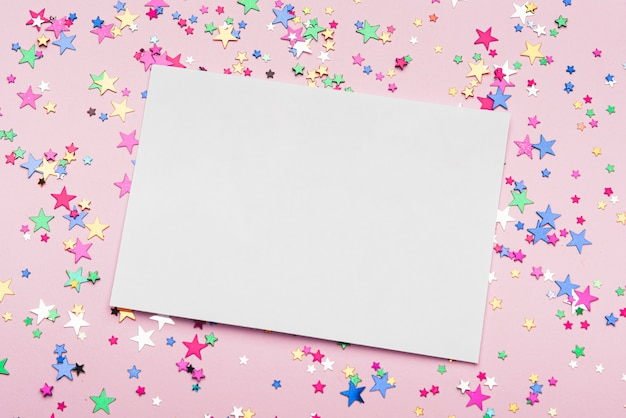 Frame with colorful confetti stars on pink background