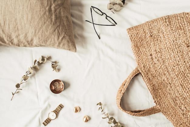 Рамка с копией пространства из модных женских аксессуаров, соломенной сумки, подушки, веток эвкалипта на белом белье