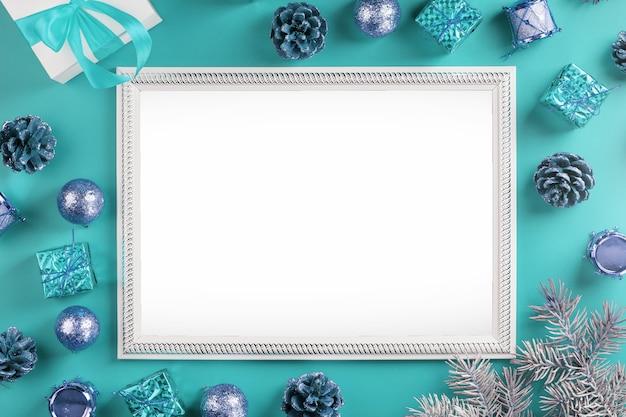 크리스마스 장식과 파란색 배경에 선물 빈 공백 프레임. 인사말 텍스트를위한 여유 공간이있는 엽서 메리 크리스마스와 새해 복 많이 받으세요.