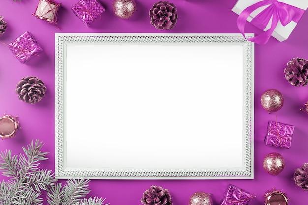 ピンクの背景にクリスマスの装飾やギフトと空の空白のフレーム。はがきメリークリスマスと新年あけましておめでとうございます。あいさつ文用の空きスペースがあります。