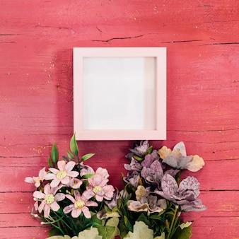 ピンクの木製の背景に花の花束を持つフレーム