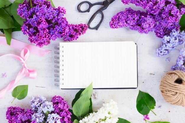 白い木製の背景に新鮮なライラックの花とフレーム、ノートブックのコピースペース