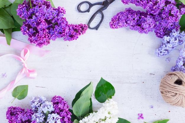 白い木製の背景に新鮮なライラックの花とフレーム