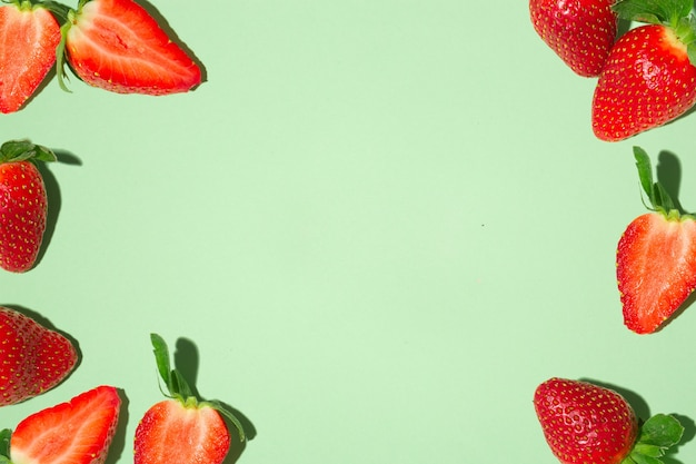 Frame with fresh red strawberries, on a green background.