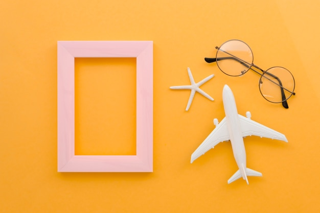 Frame with glasses and airplane beside