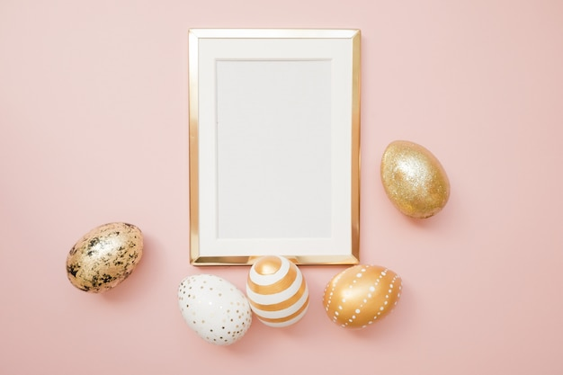 Frame with gold easter eggs on pink background.