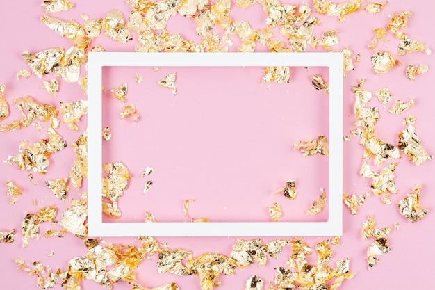 ピンクのパステルカラーの壁に金色のきらめきがきらめくフレーム。コピースペース
