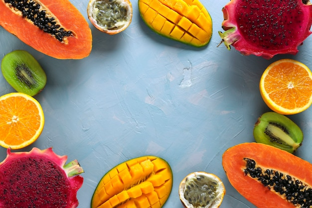 Frame with halves of tropical fruits: papaya, mango, dragon , kiwi, orange and passion fruit on a light blue surface, view from above, space for text