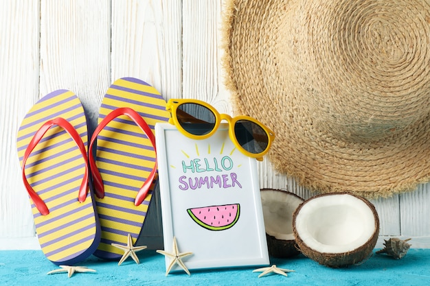 Frame with hello summer and vacation accessories on wooden, close up