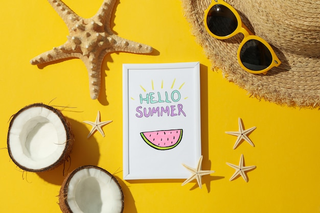 Frame with hello summer and vacation accessories on yellow surface