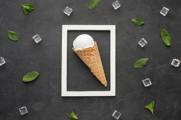 Frame with ice cream on cone inside and ice cubes