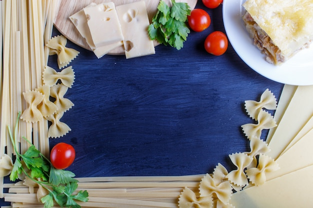Frame with italian pasta ingredients on black wooden background.