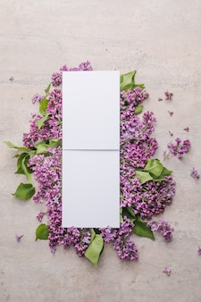 Frame with lilac flowers on grey background