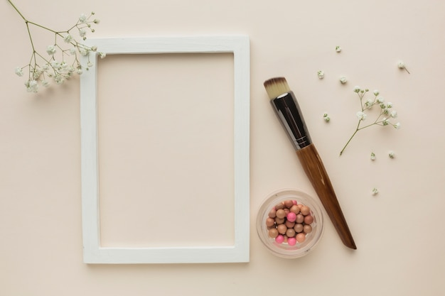 Frame with makeup products on table