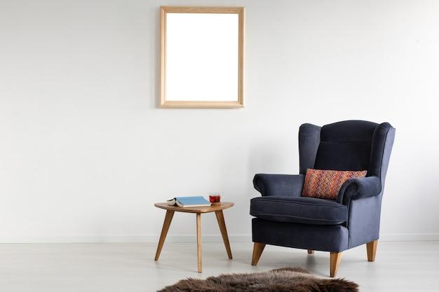 Рамка с макетом на белой стене элегантной гостиной с удобным креслом, журнальным столиком
