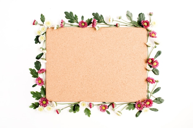 赤と白の野生の花、緑の葉、枝、白い表面に木製のコルクガシの木の板でフレーム