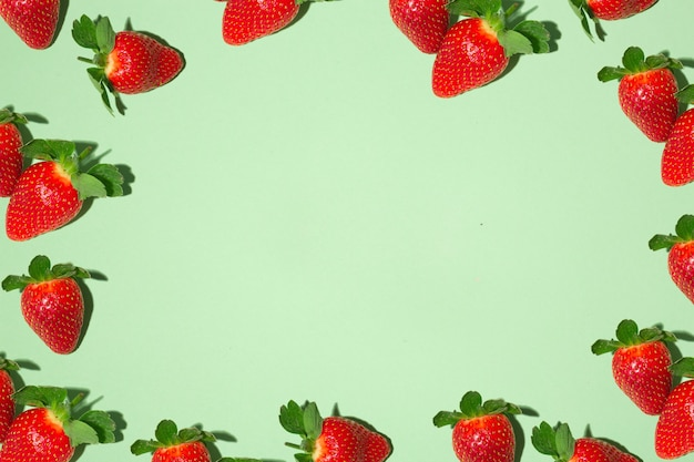 Frame with red juicy strawberries on a green background.