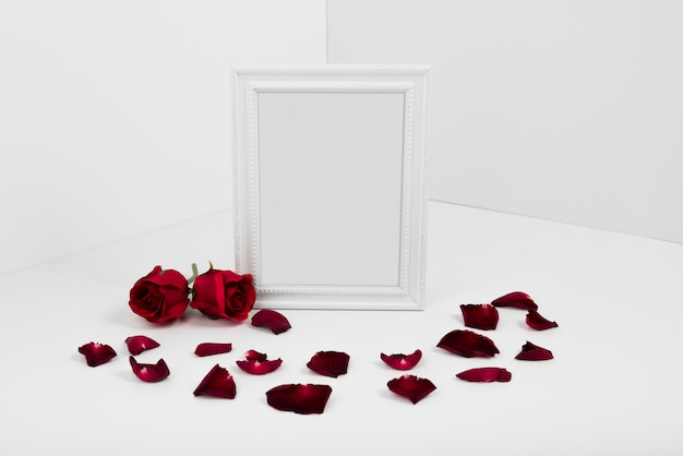 Frame with red roses on white table