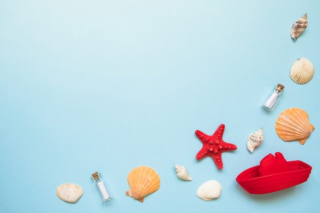 Frame with seashells, red starfish and toy boat on blue sea with copy space