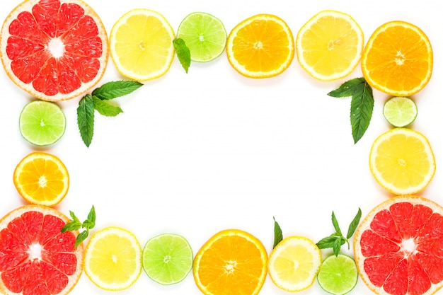 Frame with slice of oranges, lemons, limes, grapefruit and mint pattern on white