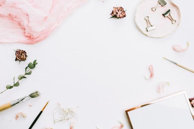 白い背景にフォト フレーム、ピンクの毛布、ユーカリの枝、バラの花のテキスト用のスペースを持つフレーム。フラットレイ、トップビュー
